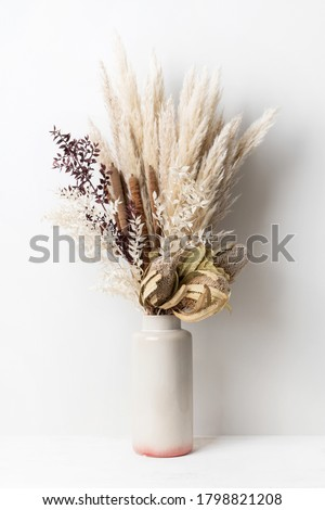 Stylish modern dried flower arrangement in a cream and pink vase. Including Banksia, pampas grass, bulrush and ruscus leaves. Art decoBoho gift for Anniversary, birthday, mothers day. Royalty-Free Stock Photo #1798821208