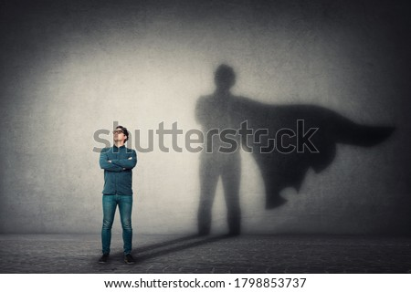 Brave man keeps arms crossed, looks confident, casting a superhero with cape shadow on the wall. Ambition and business success concept. Leadership hero power, motivation and inner strength symbol. Royalty-Free Stock Photo #1798853737