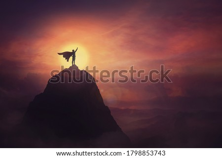 Conceptual sunset scene, superhero with cape standing brave on top of a mountain looks determined at horizon raising one hand up as a winning leader. Hero power and motivation, overcoming obstacles. #1798853743
