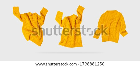 Yellow orange flying women's autumn knitted sweater on light gray background. Creative clothing concept, trendy fall winter cozy sweater pullover jersey. Women's fashion, autumn discounts. Shopping Royalty-Free Stock Photo #1798881250