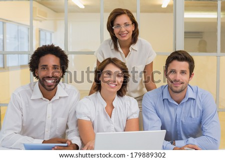 Portrait of smiling young business people using laptop together at office #179889302
