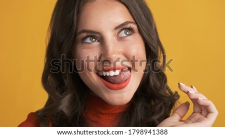 Portrait of attractive funny brunette girl happily licking teeth on camera over colorful background. Fooling around expression