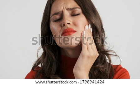 Portrait of sad brunette girl frustratedly showing teeth pain on camera over white background