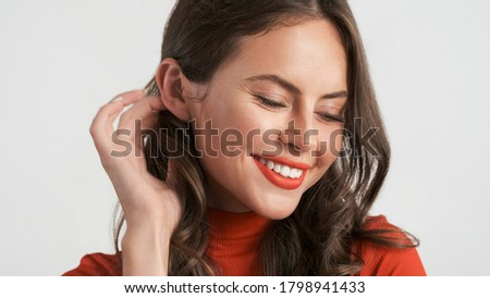 Close up beautiful smiling brunette girl charmingly posing on camera over white background