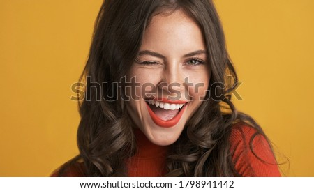 Portrait of cheerful brunette girl with red lips joyfully winking on camera over colorful background