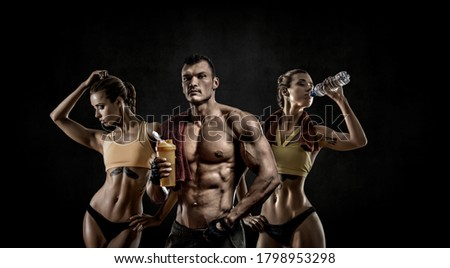 group of threesome man with woman bodybuilders hold shaker with sportive nutrition - protein of shaker on black background with empty space for text. Gym concept #1798953298