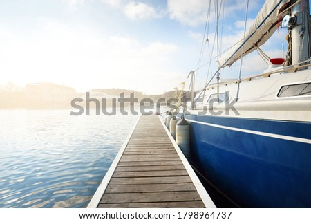 Elegant and modern sailing boats (for rent) moored to a pier in a yacht marina on a clear day. Sweden. Blue sloop rigged yacht close-up. Vacations, sport, amateur recreational sailing, cruise Royalty-Free Stock Photo #1798964737