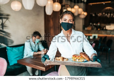 Beautiful young waitress with face protective mask serving delicious burger to middle age male customer. Corona virus and small business is open for work concept. #1798966315