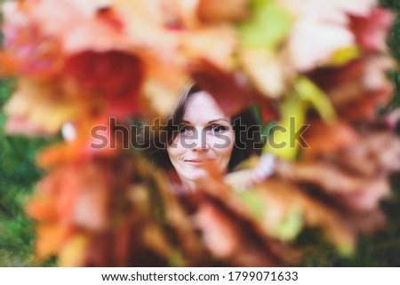 Brunette caucasian happy woman in circle frame of maple leaves wreath. Autumn harvest, nature concept. Flowers bouquet of orange, red, yellow leaves. Park, garden, forest fall photo shoot.