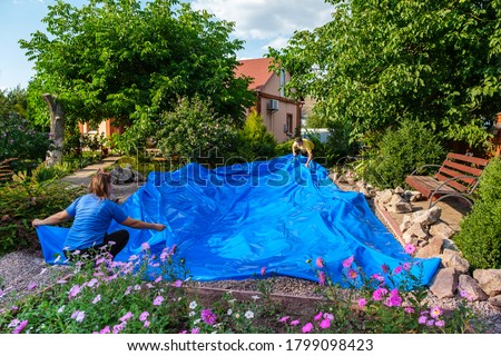 Family lays a blue HDPE plastic sheet on the ground to set up a fish pond