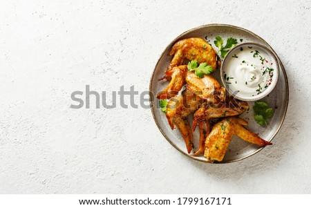 Baked chicken wings with herbs and dip. Royalty-Free Stock Photo #1799167171