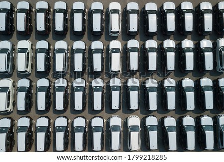 Aerial view shot from a drone of new cars parked in rows on a lot ready for exporting to other countries.