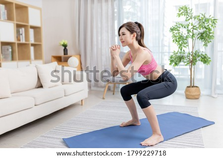 asian young woman is doing squats exercise at home #1799229718
