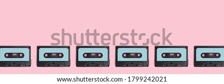 Row of cassette tapes on a pink pastel background. Creative banner with place for text.