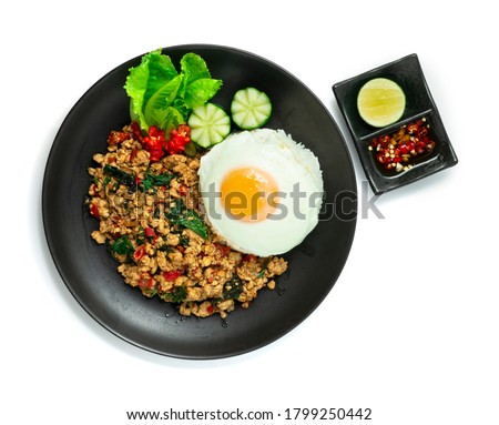 Spicy Chicken  Stir Fried with Basil,chili and Rice ontop Fried Egg decorate Carved chili and vegetable served Chili fish Sauce Thai Food style topview #1799250442