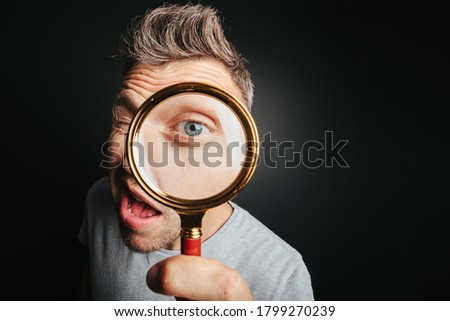 man see through magnifying glass on the black backgrounds. Big man eye Royalty-Free Stock Photo #1799270239