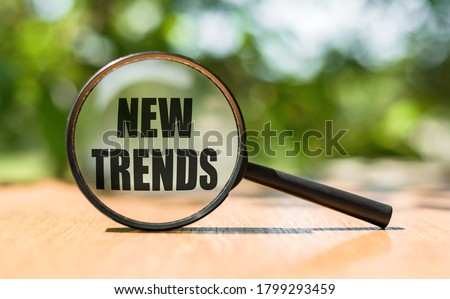 NEW TRENDS text written on magnifying glass. Main trend of changing something. Popular and relevant topics. New trends in business. Recent and latest trend. Evaluation methods. Royalty-Free Stock Photo #1799293459