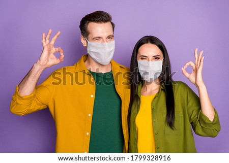 Close-up portrait of his he her she nice attractive healthy couple wearing safety mask health care insurance embracing showing ok-sign winking isolated violet purple color background #1799328916