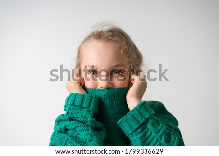 charming little girl hides her lower face under the thick collar of a warm knitted sweater. Children, gestures and emotions, happiness, winter. Close up studio shot isolated on white, copy space Royalty-Free Stock Photo #1799336629