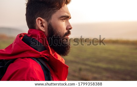 Side view of young bearded male hiker in warm red jacket looking away while standing against blurred green field during trekking in autumn countryside Royalty-Free Stock Photo #1799358388
