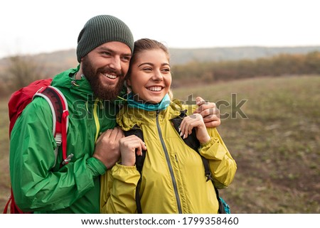 Cheerful young man and woman in colorful outerwear with backpacks laughing and looking away while standing together in autumn field during hiking Royalty-Free Stock Photo #1799358460
