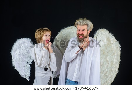 Father and son Angels. Valentines angels. Happy father with little son in angel costumes. Valentines day. Cute angel. Little cupid boy gives father gift. Halloween angels. #1799416579