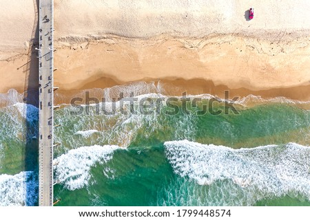 A Pier road to the sea and a red car on coast with lovely waves in Manhattan Beach - Aerial View Royalty-Free Stock Photo #1799448574