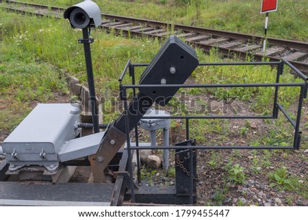 Mechanism of crossing barrier device is to raise barrier on asphalt road when train passes along railway track. Gray box with control electronics, motion sensor and large metal lever to counterweight #1799455447