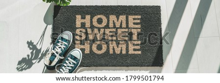 Home sweet home door mat at house entrance with women's sneakers of woman that has just arrived. New condo homeowner moving in with plant. Panoramic crop. Royalty-Free Stock Photo #1799501794