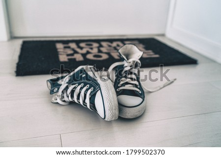 Leaving shoes on floor, at front door entrance outside home. Men removing their sneakers without placing them away. Tidy house cleaning concept. Royalty-Free Stock Photo #1799502370