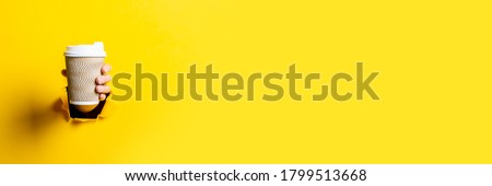 Female hand holding a paper cup of coffee with the lid closed on a bright yellow background. Banner. Royalty-Free Stock Photo #1799513668