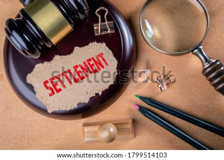 SETTLEMENT. Laws, litigation, lawyers and compromise concept. Wooden court hammer and magnifying glass on the table Royalty-Free Stock Photo #1799514103
