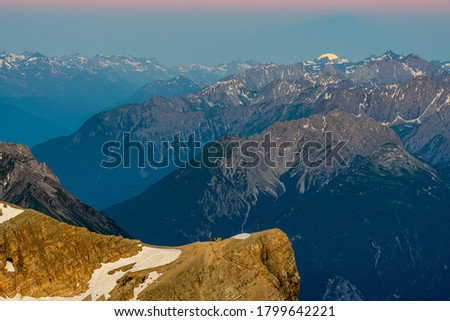 The full moon over the alpine moutains. Picture was taken on the summit Zugspitze, highest mountain in Germany.