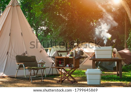 Outdoor kitchen equipment and wooden table set with field tents group in camping area at natural parkland #1799645869