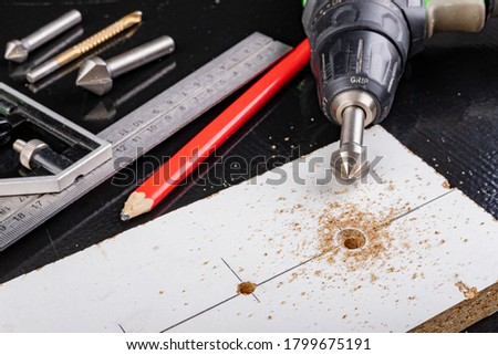 Metal countersink for making holes for screws. Minor jobs in the carpentry workshop. Light background. #1799675191