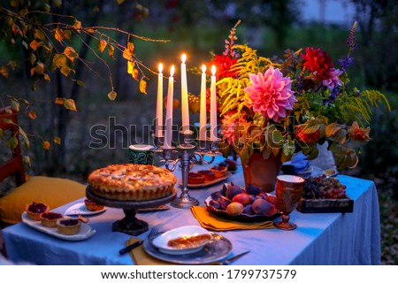 Autumn evening photo shoot - romantic dinner outdoors. Table with tablecloth and decoration - pie, figs, glasses, plates, table setting and candelabra with candles. Fall flowers dahlia bouquet.