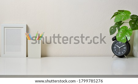 Modern workspace with frame picture, coloured pencil, clock and vase on white table in office. Front view.