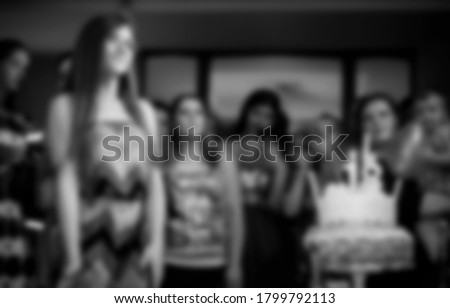 Blurred people at birthday party, black and white image for background use.