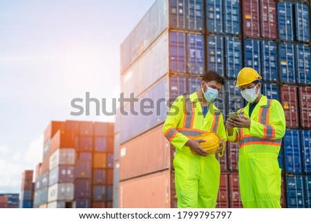 Engineer or worker man using a smartphone wearing mask and safety yellow helmet to protection for coronavirus in during concern about covid pandemic.Workers wearing protective mask working in cargo. Royalty-Free Stock Photo #1799795797