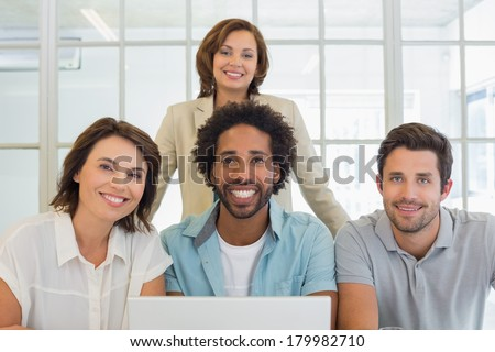 Portrait of smiling young business people using laptop together at office #179982710