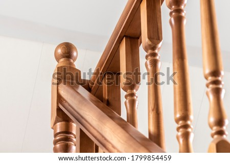 Element of a wooden interior staircase. Wooden baluster close-up. Royalty-Free Stock Photo #1799854459