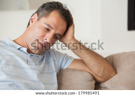 Close-up of a thoughtful man sitting on sofa in the living room at home #179985491