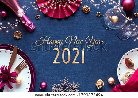 Happy New Year 2021 gilded text in frame made from Silvester party table setup. Vine, glasses, plates, fork, knife. Xmas decorations and garland. Flat lay in golden and red on classic blue textile. #1799873494