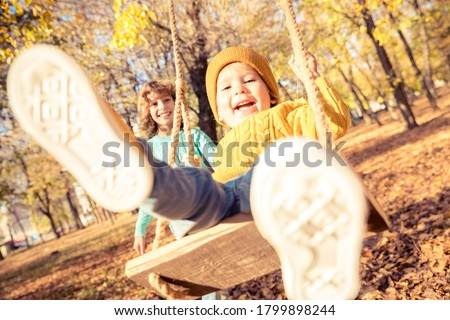 Happy children having fun outdoor in autumn park. Kids playing on swing against yellow blurred leaves background. Freedom and carefree concept Royalty-Free Stock Photo #1799898244