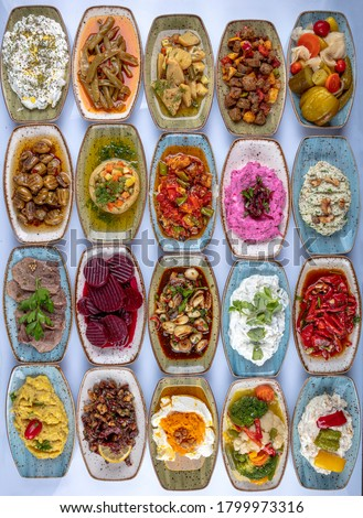 Traditional Turkish and Greek dinner meze table. Turkish Cuisine Cold Appetizers (appetizers with olive oil). Turkish appetizers in colorful plates. yogurt and various boiled herbs #1799973316