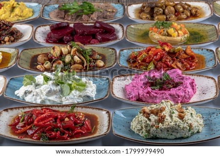Traditional Turkish and Greek dinner meze table. Turkish Cuisine Cold Appetizers (appetizers with olive oil). Turkish appetizers in colorful plates. yogurt and various boiled herbs #1799979490