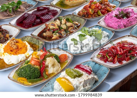 Traditional Turkish and Greek dinner meze table. Turkish Cuisine Cold Appetizers (appetizers with olive oil). Turkish appetizers in colorful plates. yogurt and various boiled herbs #1799984839