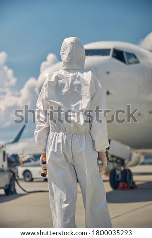 Back view of a female dressed in a protective suit standing in front of the airliner #1800035293