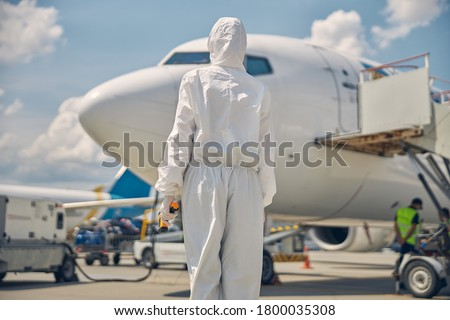Back view of an airline female employee in a hazmat suit standing in front of the aircraft #1800035308