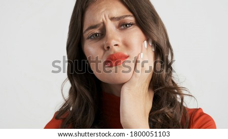Upset brunette girl sadly looking in camera showing teeth pain over gray background
